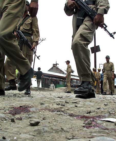 Policemen inspect the place in Batamaloo Srinagar where militants shot and injured a Special Police Officer on Friday
